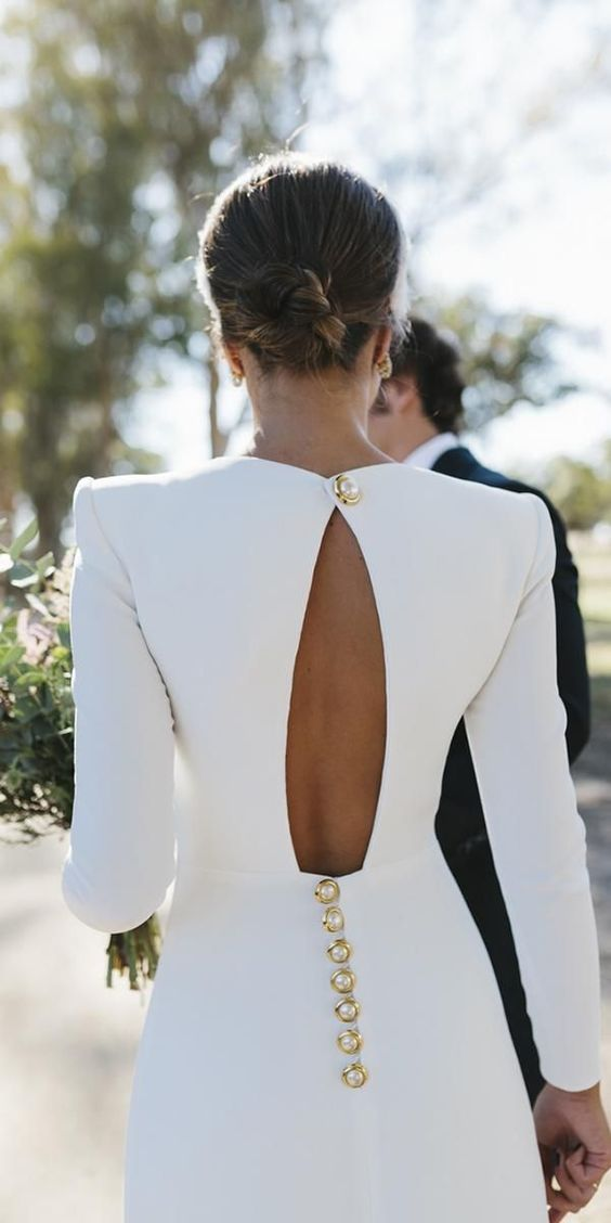 a cutout back with a statement gold and pearl button and a row of matching buttons below