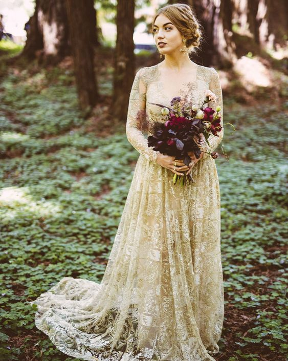 a gold wedding dress with white lace appliques, with a deep neckline and long sleeves for a dramatic look
