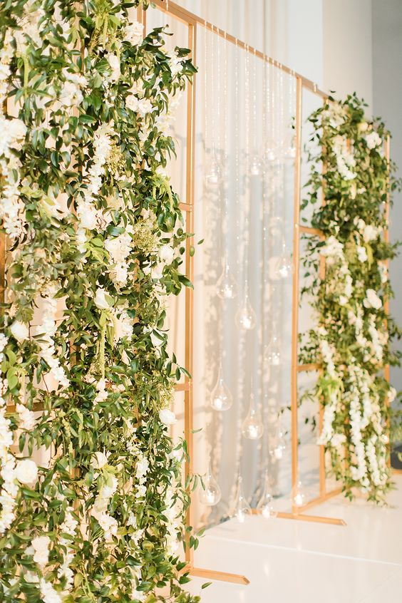 a gorgeous wedding backdrop with a gold frame, white blooms and greenery and hanging candleholders