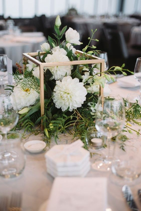 a gorgeous white and gold wedding centerpiece of a gold frame, greenery and white blooms plus candles