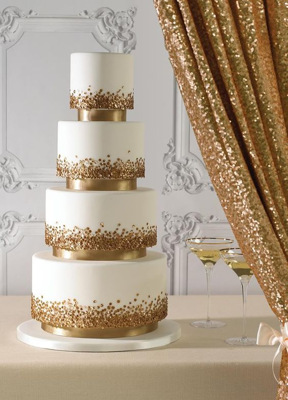 a jaw dropping wedding cake in white, with gold polka dots looks very chic and very glam like