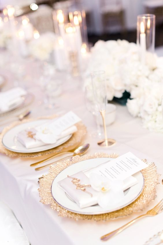 a luxurious wedding table setting with gold chargers, cutlery, white blooms and gold glasses is chic