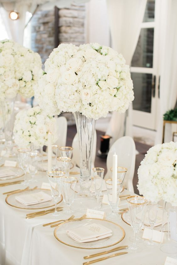 a luxurious wedding tablescape with oversized white centerpieces, gold edge plates and glasses and gold cutlery