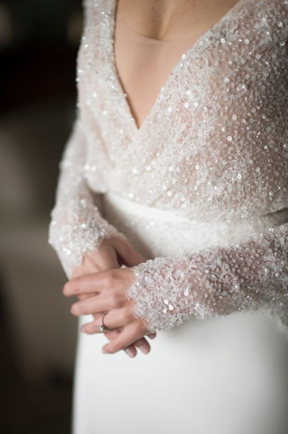 a modern glam wedding dress with pearls and sequins on the bodice and long sleeves contrast the plain skirt