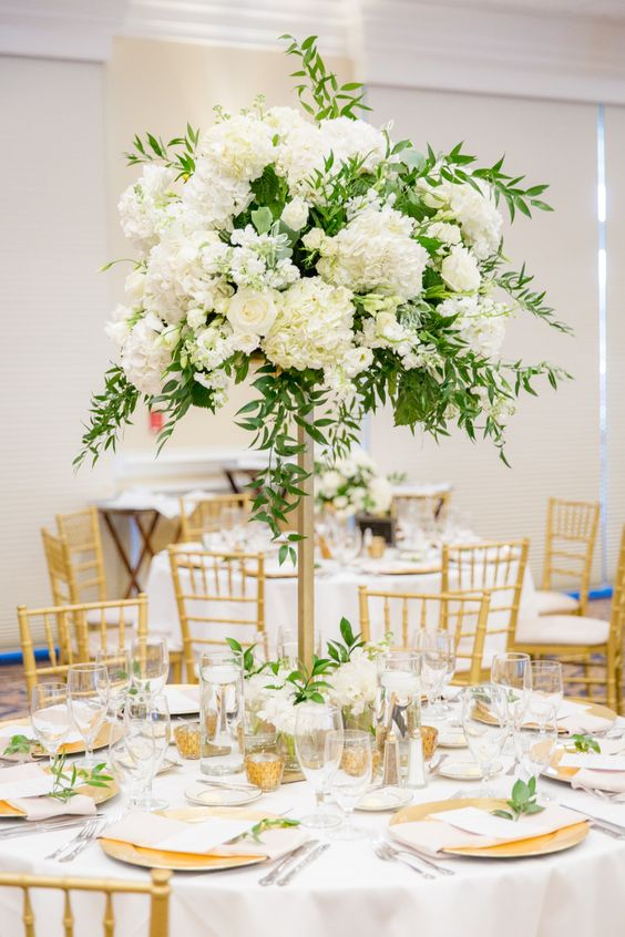 a pretty and chic wedding tablescape with gold chargers, candleholders and cutlery, white blooms and greenery