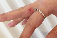 a red heart tattoo on the side of the finger is a cool and cute idea in a bold color but still rather hidden