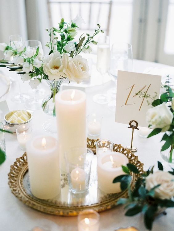 a refined wedding centerpiece of a mirror tray, candles, white roses and greenery and a table number