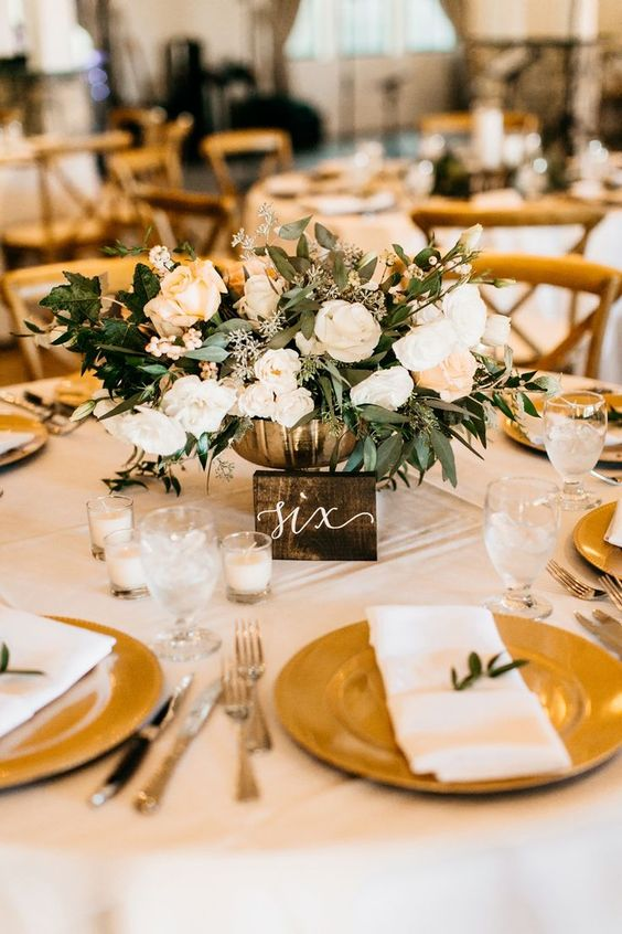 a refined white and gold wedding tablescape with white florals and greenery, candles, gold chargers and silver