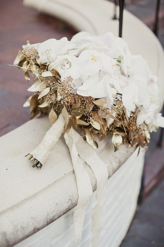 a refined white wedding bouquet spruced up with gold foliage is a very stylish and chic idea