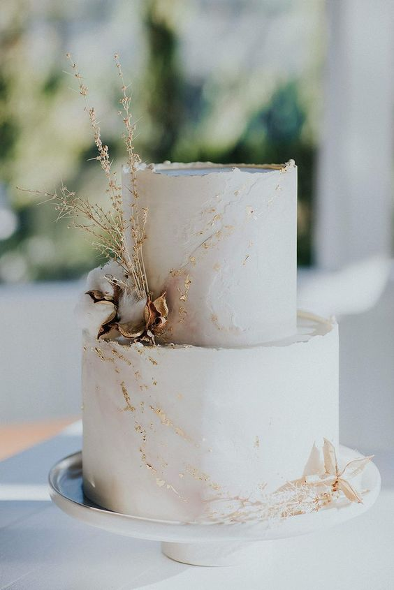 a refined white wedding cake with a rough edge, gold leaf, dried blooms and greenery is a very chic idea