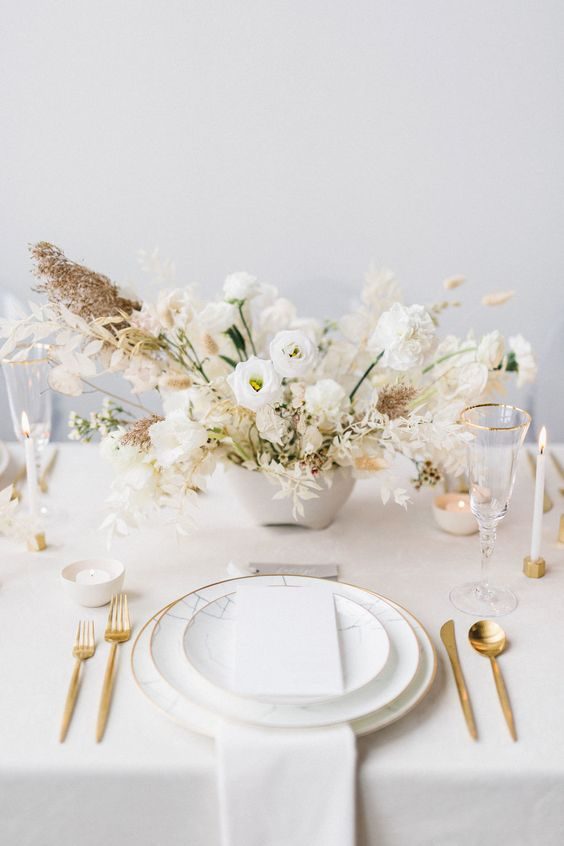 a stunning wedding tablescape with a white floral arrangement, candles, gold cutlery and white plates