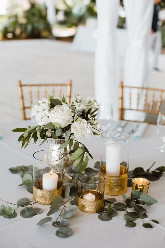 a stylish wedding centerpiece with greenery, white blooms and gilded candleholders for a white and gold wedding
