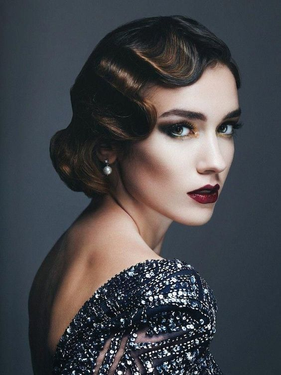 a super chic wavey low updo with color accents and a matching makeup for a modern yet vintage-inspired bride