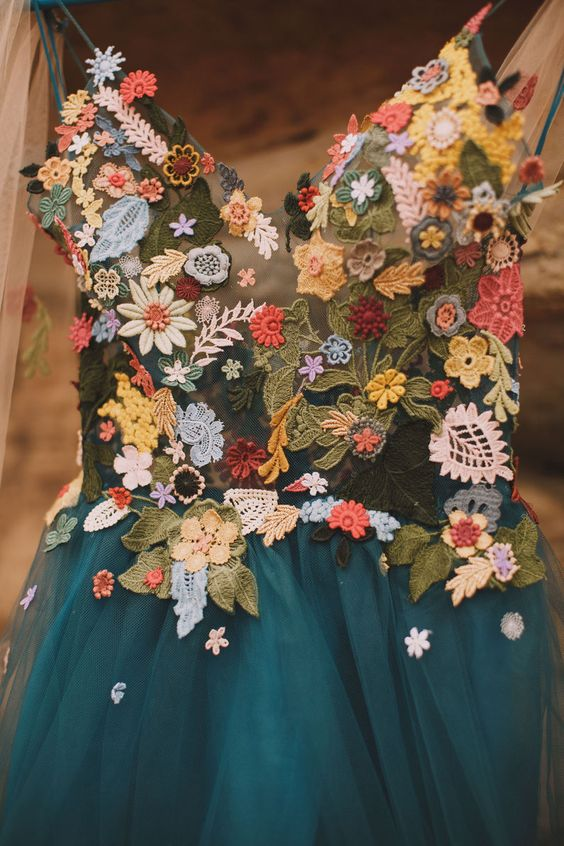 a teal wedding dress with a sheer bodice fully covered with colorful floral and leaf crochet on spahgetti straps