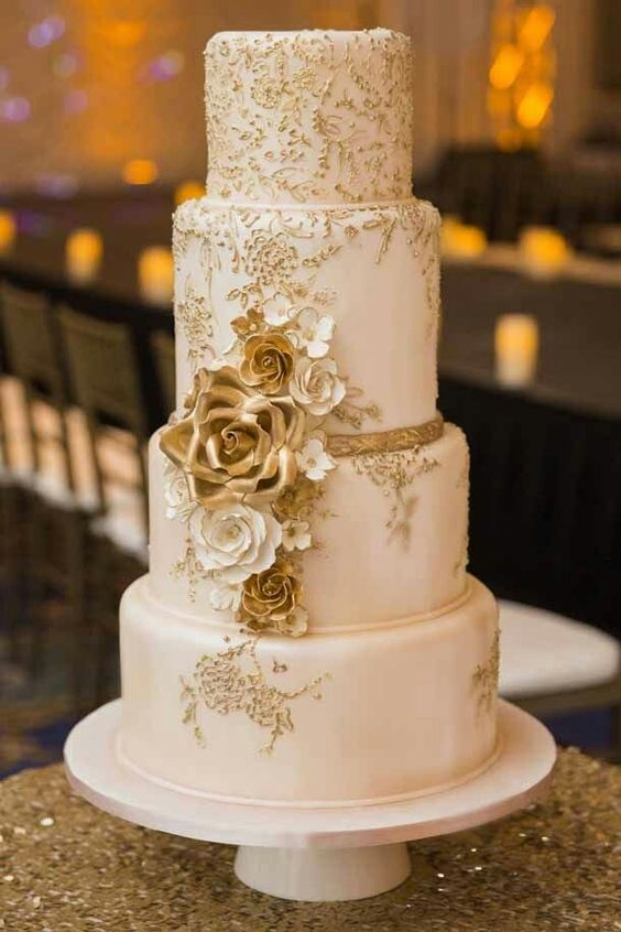 a vintage-inspired wedding cake in white and gold, with floral patterns, white and gold sugar blooms and ribbons