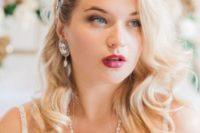 a vintage wavy hairstyle with an embellished hairpiece on one side and a glam makeup with a fuchsia lip
