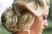 a vintage wavy low updo with a large bun and some locks down for ultimate elegance