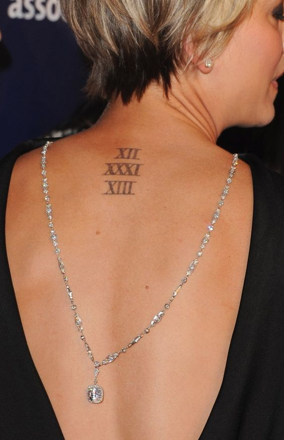 a wedding date tattoo made with Roman numbers on the back and accented with a necklace by Kaley Cuoco