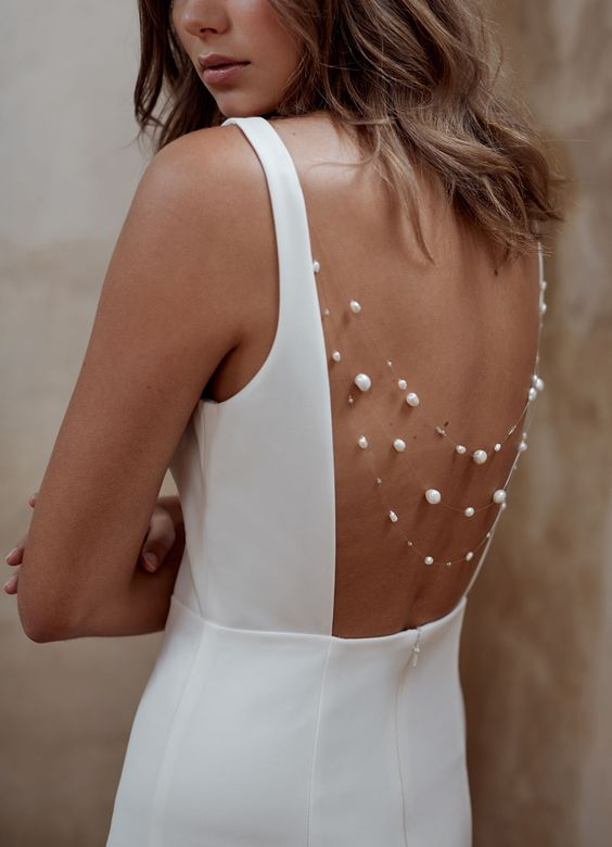 a white minimalist wedding dress with an open back and strands of baroque pearls to accent it