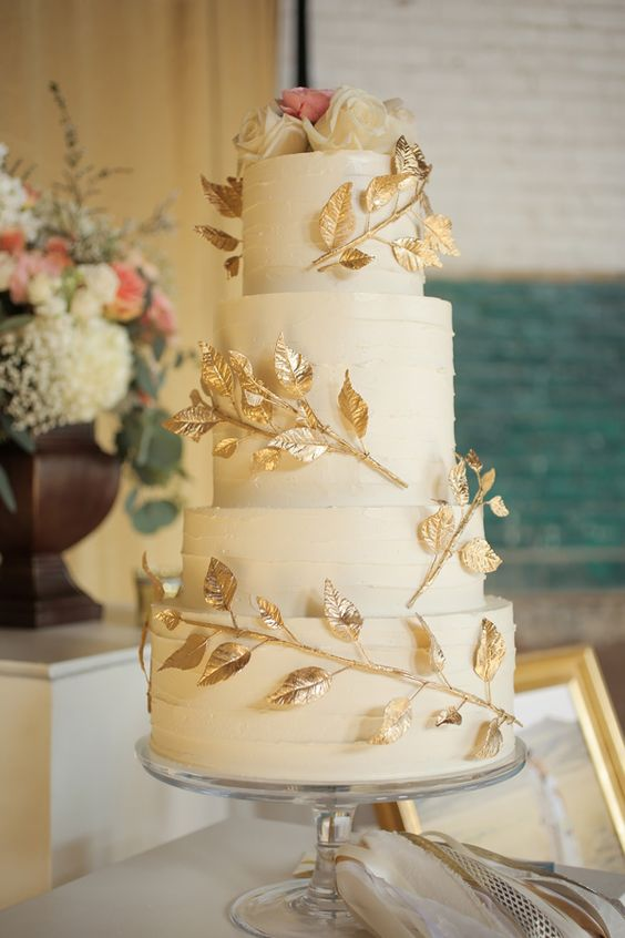 a white textural wedding cake with gilded leaf branches and white and pink roses on top