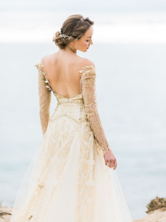 an off the shoulder white and gold patterned open back wedding ballgown with long illusion sleeves