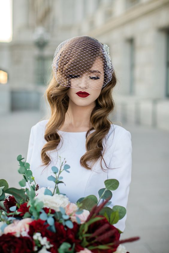 long vintage waves accented with a birdcage veil and a burgundy lip look very elegant and vintage-inspired
