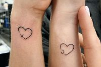 small heart tattoos with monograms on the sides of the wrists are cute, chic and very meaningful