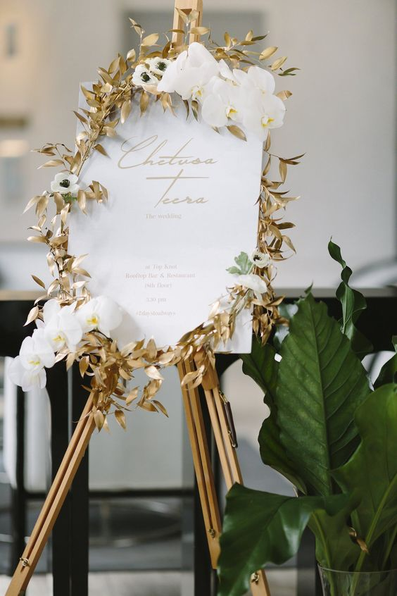 wedding signage with gilded foliage, white orchids and gold printing is a very refined and beautiful idea