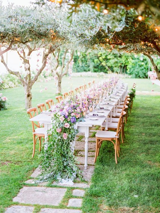 a beautiful outdoor spring wedding reception with pink blooms hanging on the trees, a lush table runner of bright blooms and greenery