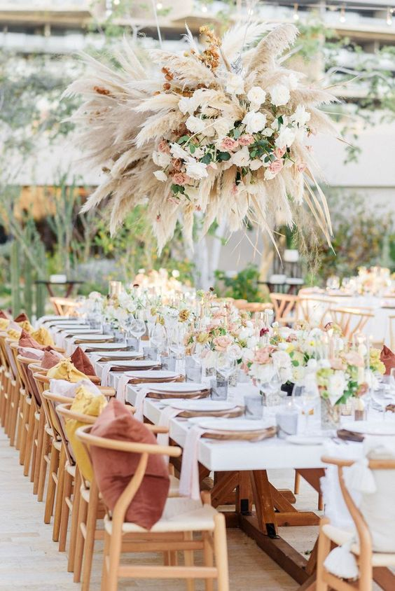 a bright and chic spring wedding reception with bright blooms, greenery, a lush chandelier of pampas grass and blush flowers