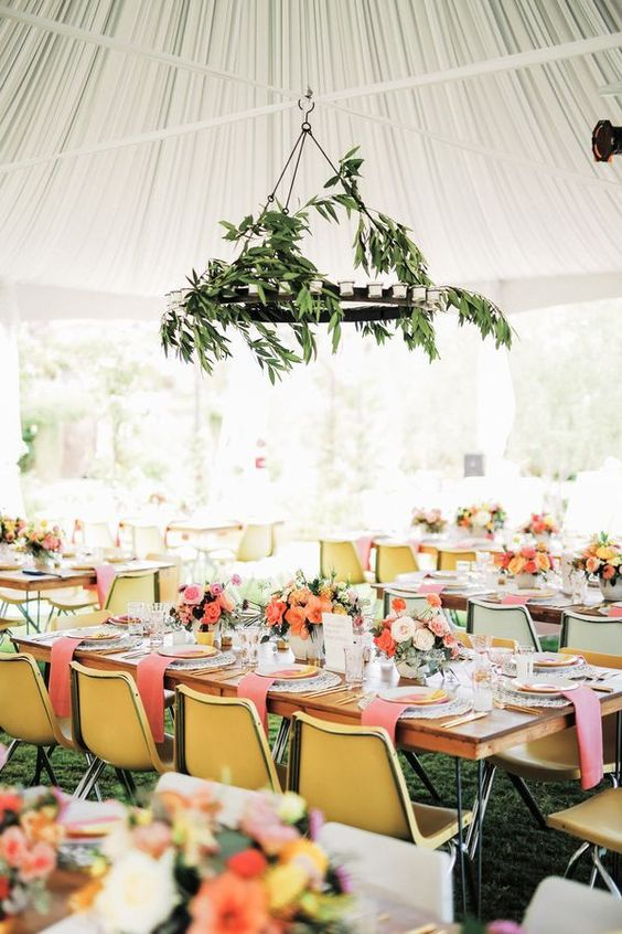 a bright spring wedding reception with a greenery chandelier, bright linens and chairs and colorful blooms