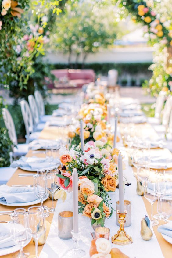 a bright spring wedding reception with colorful blooms and greenery, white candles, white linens and lots of greenery over the table
