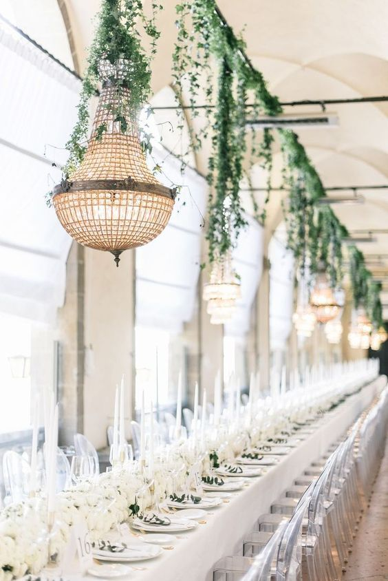 a chic formal wedding reception with greenery decor and chandeliers, white blooms and candles