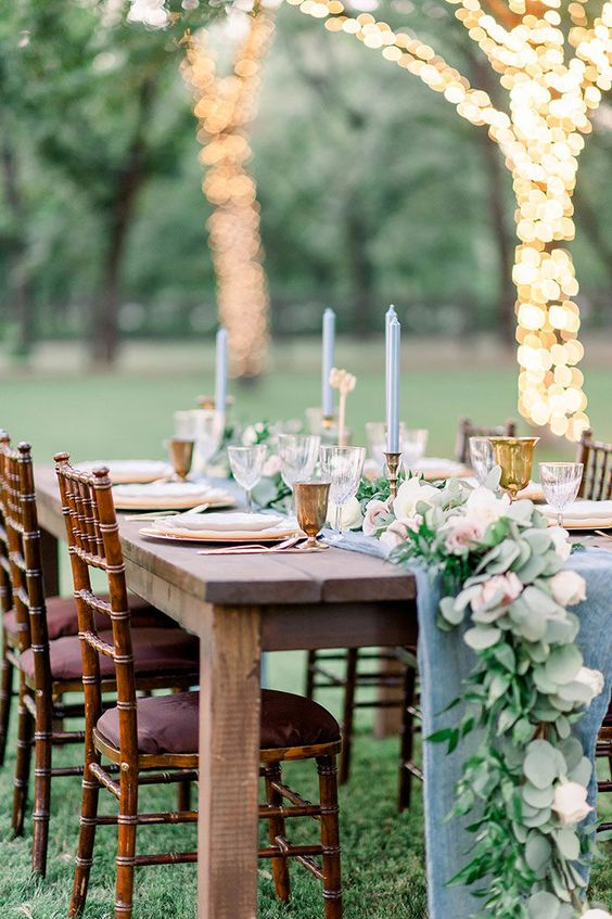 a cute pastel spring wedding reception with blue runners and candles, a lush table runner of greenery and pink flowers and light wrapped trees