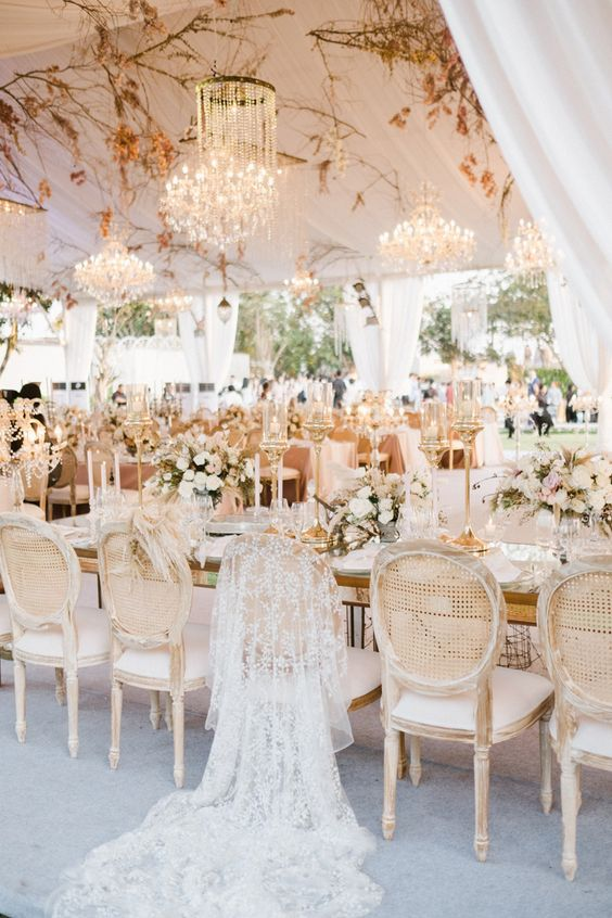 a luxurious formal wedding reception with dried greenery over the tables, shiny chandeliers, white blooms in vases