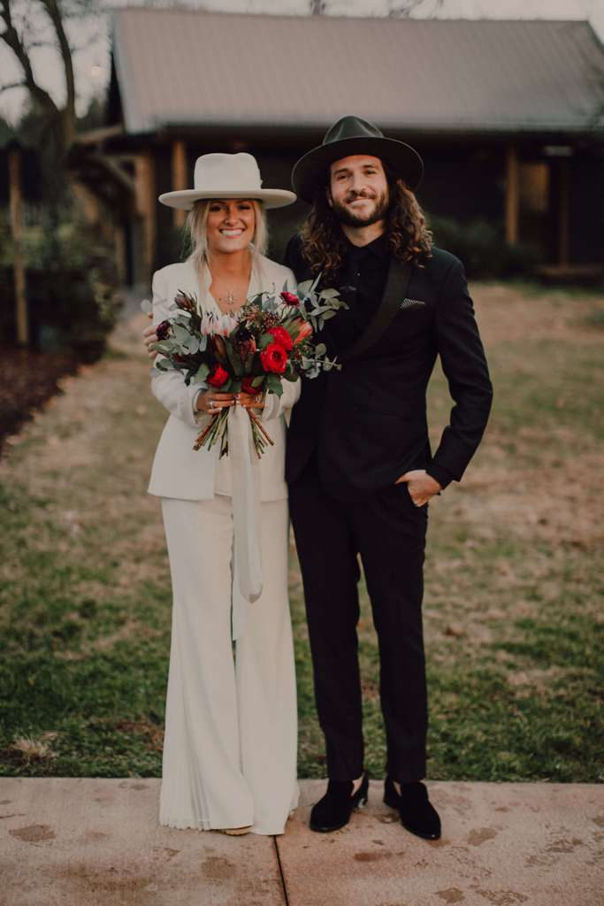 a modern boho bride wearing a white pansuit with a white shirt, a white hat and platform heels