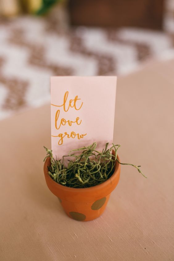 a pot with grass and a card compose a simple and very cute spring wedding favor