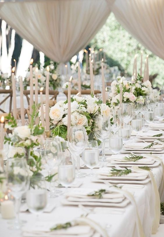 a refined and formal wedding reception with white blooms, blush candles, greenery and elegant white linens
