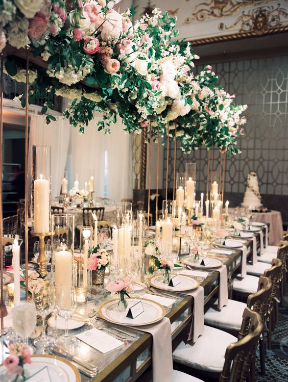 a refined formal wedding reception with a lush decoration of blush blooms and greenery overhead, lots of candles and pink flowers