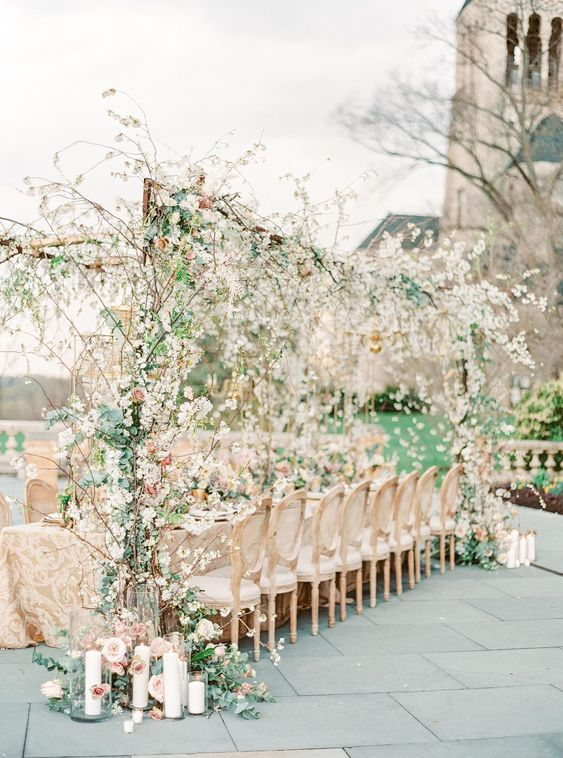 a romantic outdoor blooming wedding reception with lush blooming branches over the table, candles, ivory linens and white chairs