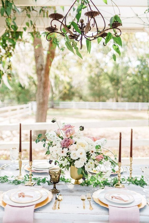 a romantic vintage glam wedding reception with greenery chandeliers, a pastel floral centerpiece and pastel linens