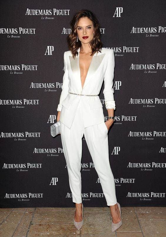 a sexy modern white pantsuit with shiny lapels and pockets plus off-white shoes and a clutch