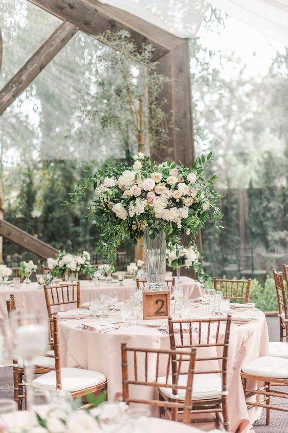 a spring wedding reception with blush linens, tall centerpieces of blush and white blooms and greenery