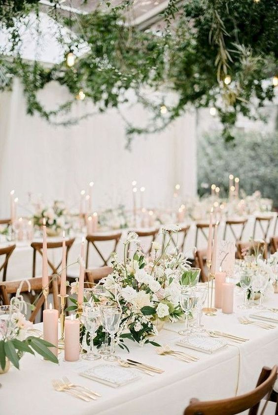 a spring wedding reception with greenery over the tables, blush candles, white blooms and greenery on the tables and gold touches