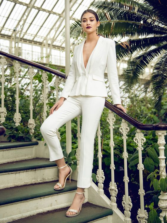 a stylish modern white pantsuit with no tops on and silver shoes for a modern or minimalist look