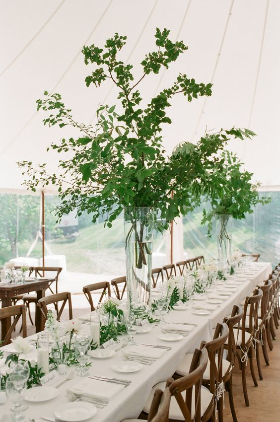 a stylish spring wedding reception with tall greenery centerpieces, white blooms and candles and linens