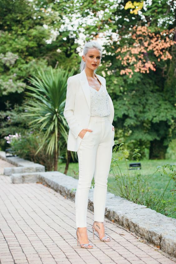 a stylish white pantsuit, a white fully embellished top and silver embellished shoes for an edgy look