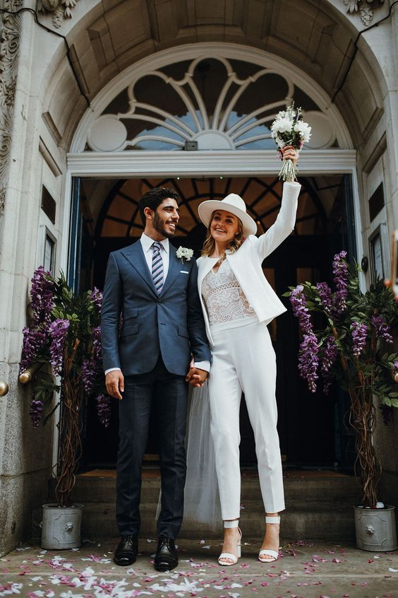 a stylish white pantsuit, a white lace bodysuit, white heels and a white fedora for a modern bride