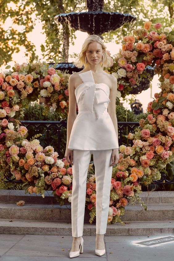 a whimsy white pantsuit with fitting pants, a strapless bow top and neutral shoes