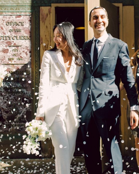 a white modern pantsuit with a white top and a long blazer for a modern and simple wedding